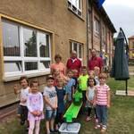 Martina Leipold (Leiterin der Einrichtung), Ralf Wunschinski (Bürgermeister) und Olaf Runge (Geschäftsführer EURONICS GmbH) mit den Kinder der Kita 'Max und Moritz'